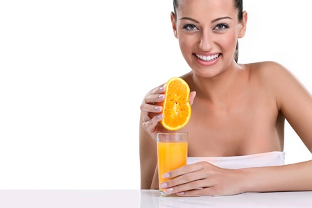 squeeze:  young smiling woman squeezes orange juice into a glass