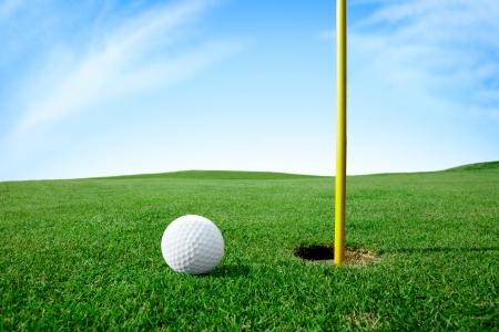 Balle de golf sur l'herbe verte trou suivant Banque d'images