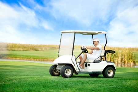 buggy: Young man driving golf buggy on golf course