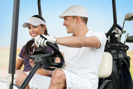 Couple smiling and driving in buggy in golf course photo