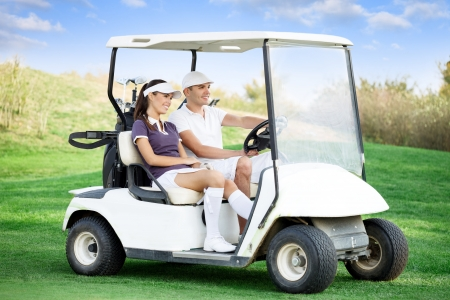 golfing: Young couple driving golf cart