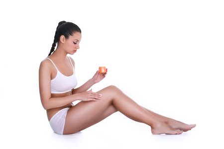lotions:  woman applying lotion on her body, creaming the legs