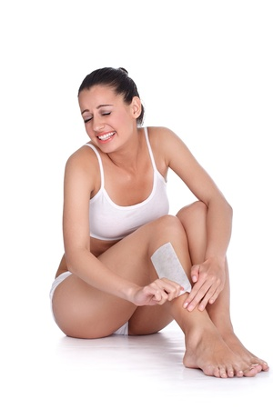 Beautiful woman doing depilation with waxing, expressing pain on face photo
