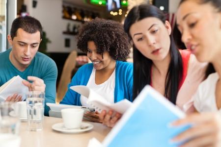 socializando: Grupo de aprendizaje de los estudiantes juntos en la cafetería Foto de archivo