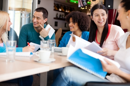 woman speaking: Young students discussing in cafe Stock Photo