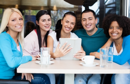 socializing:  Smiling group of teenagers at cafe with tablet touch