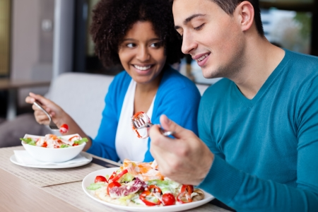 pareja comiendo: Encantadora pareja interracial de almorzar en el restaurante Foto de archivo