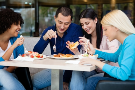 having lunch:  Young people having lunch in restaurant, smiling and talking Stock Photo