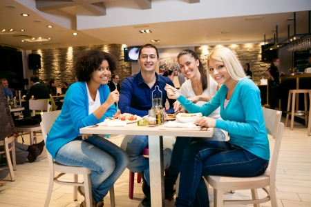 socializing: Group of young people having lunch in restaurant