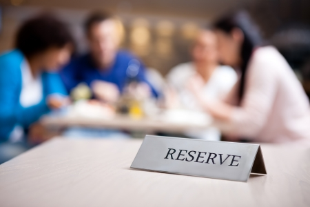reserved table at nice restaurant with guests in the background photo