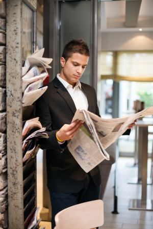 Young businessman reading newspaper photo