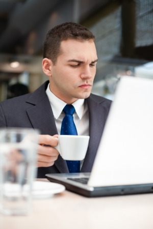 surf shop:  young man with a cup and a laptop in a cafe