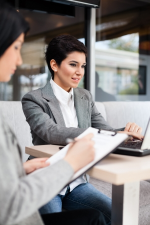 Two businesswomen with paperwork on meeting Stock Photo - 17821934