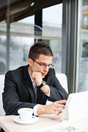 Good-looking manager sitting at desk, using tablet in cafe Stock Photo - 17803963
