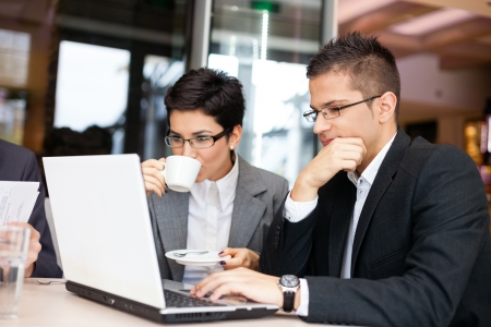 businesswoman and  businessman using laptop in cafe photo