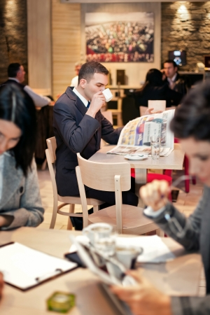 Young businessman sitting at table in cafe, drinking coffee and reading magazine. photo