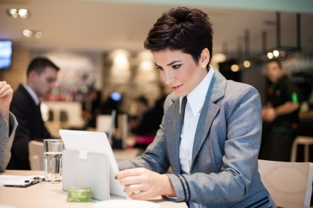 cafe internet: Empresaria que trabaja en contacto tableta en pausa para el café
