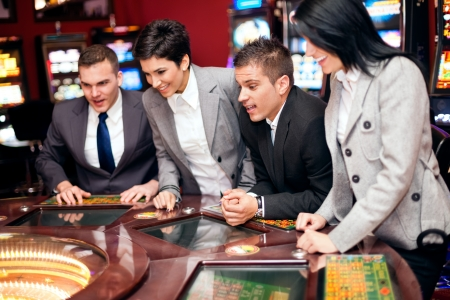 business game:  Excited people looking at spinning roulette in casino