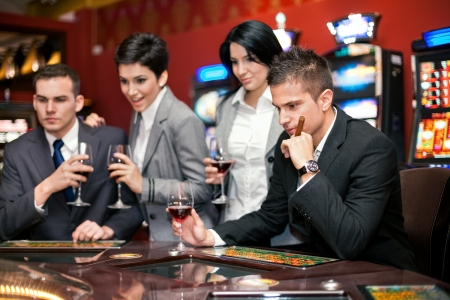 roulette player:  group of young smiling people looking excited at spinning roulette Stock Photo