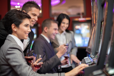 Young people enjoying to play slot machines at casino photo