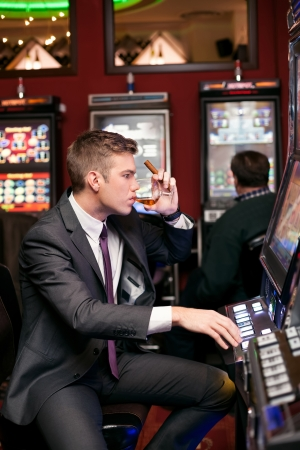handsome man being concentrated in playing the slot machine photo