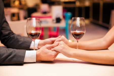 Man and woman at the restaurant - holding hands together photo