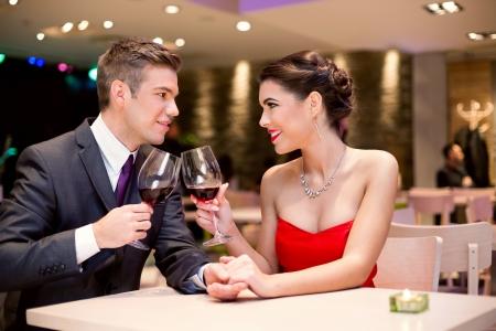 ciascuno: felice coppia affettuoso al ristorante tostatura e guardando gli altri