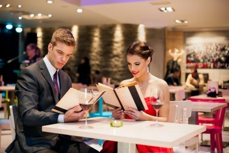 diner romantique: jeune couple heureux dans le menu lecture Restaurant Banque d'images