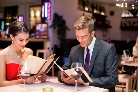 diner romantique: jeune couple heureux dîner à l'extérieur dans le restaurant et la lecture du menu