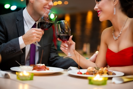 Attractive young couple drinking red wine in a romantic atmosphere