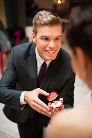 arrodillarse: Hombre joven romántico que propone a la novia y ofreciendo anillo de compromiso