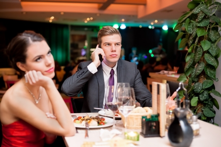 business dinner:  young woman bored to date while her boyfriend having business cell on mobile phone
