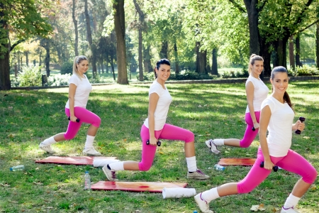 Group of smiling women doing exercise with dumbbell photo