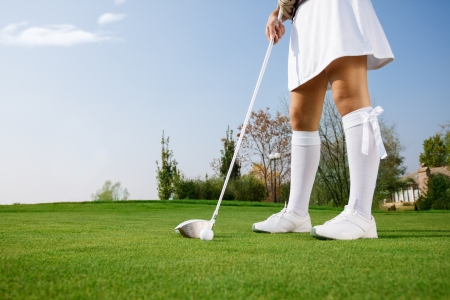 Woman golfer  putting ball,  golfing on the green photo