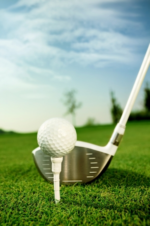 golf equipment:  Golf equipment, golf ball with tee on course and stick  Stock Photo