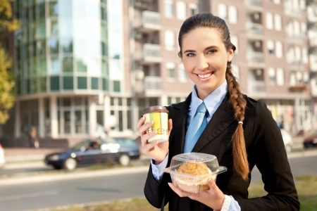 smiling businesswoman with her breakfast, outdoor photo