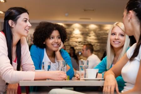 socializando: Cuatro mujeres jóvenes con coffee break
