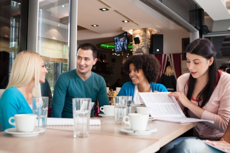 pleasure of reading: Four young students consulting in cafe