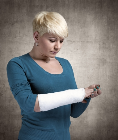 Sad woman looking in  cast on her arm. photo