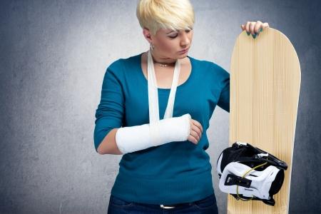 brazo roto: Snowboarder Descontento con el brazo quebrado mirando de snowboard Foto de archivo