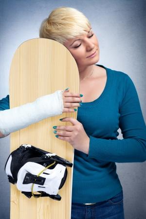 brazo roto: Mujer con fractura de brazo que abraza a su tabla de snowboard, me encanta el snowboard