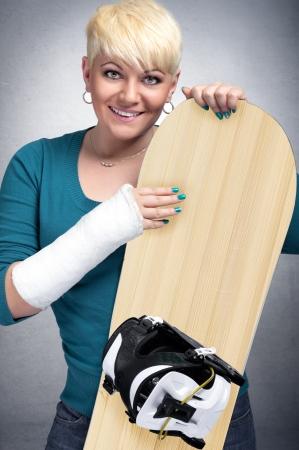 brazo roto: Mujer snowboarder alegre con el brazo roto Foto de archivo