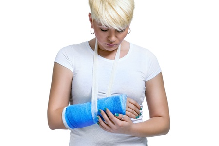 arm in arm:  Young woman holding painful arm in blue cast on a white background