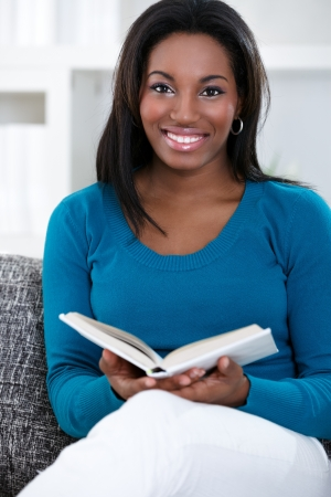 south american ethnicity:  Relaxed black woman sitting on sofa enjoying reading book