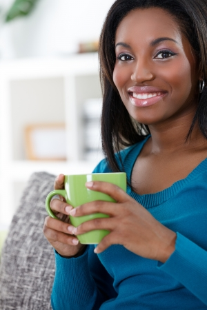 south american ethnicity: Young African woman enjoying in coffee or tea
