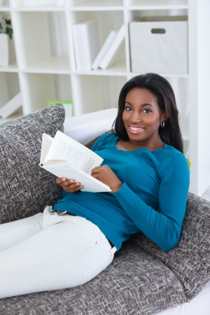 black woman reading book in living room Stock Photo - 19404870