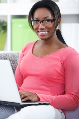 Cheerful student girl in living room with laptop Stock Photo - 19405011