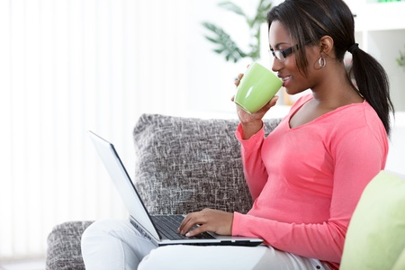 using the laptop: Black woman using a laptop while having a tea in her living room Stock Photo