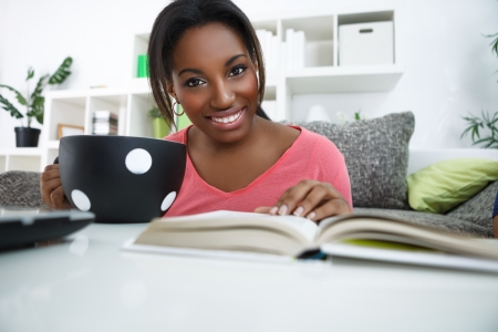 south american ethnicity: Cheerful young African student with big cup of coffee learning at home