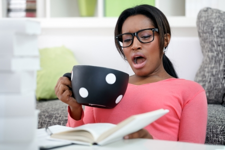 tired female student yawning with big cup of coffee photo